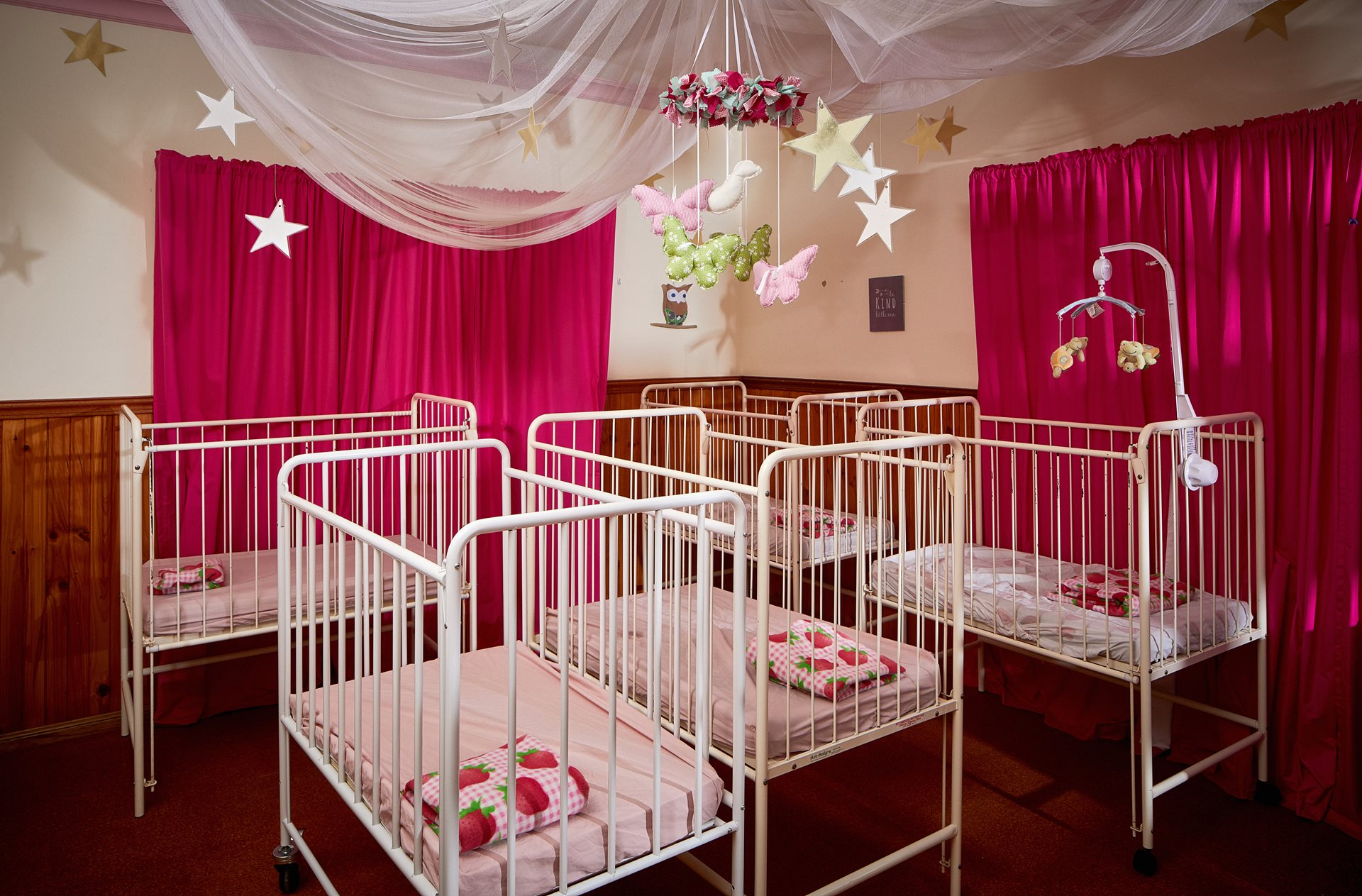 Nursery room at child care centre with cots and mobiles